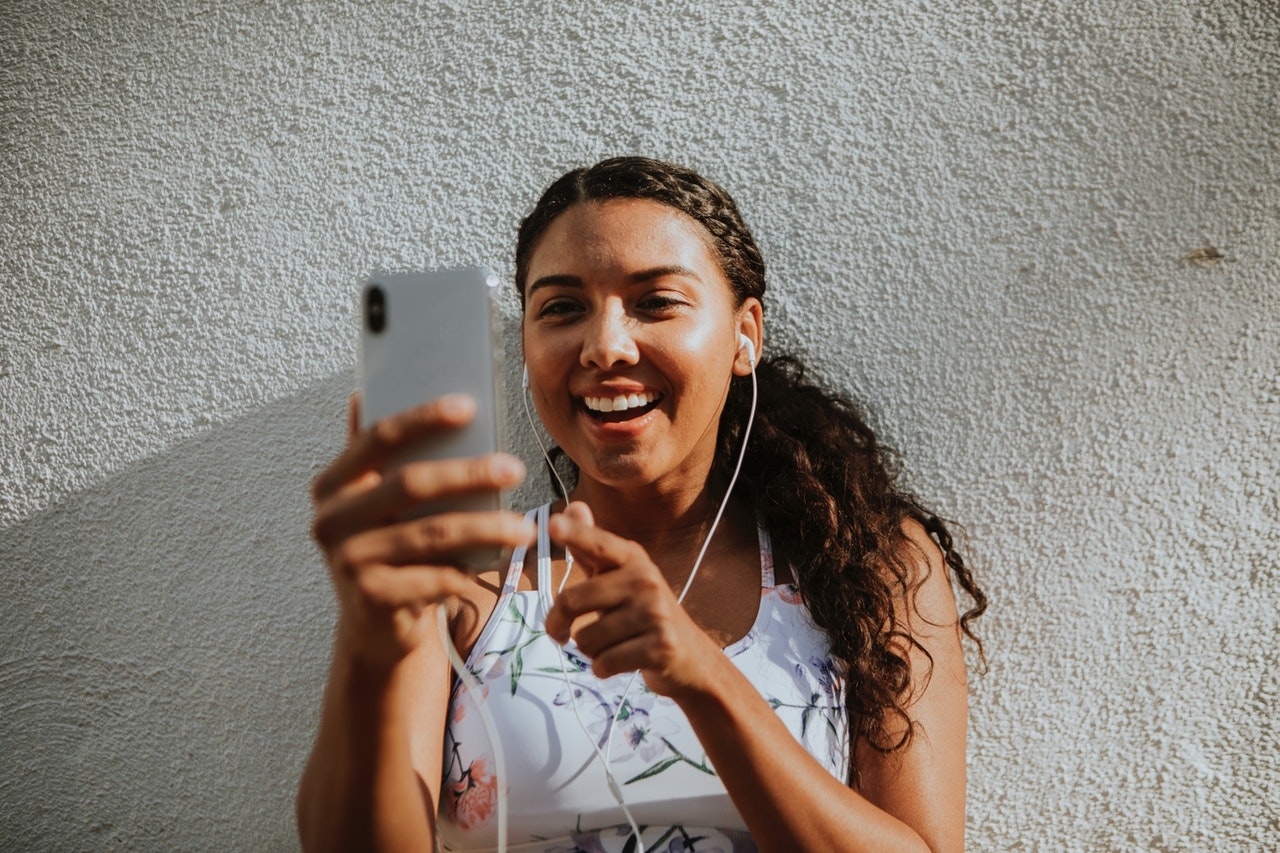 Woman Using Silver Iphone X While Leaning on Wall and Smiling
