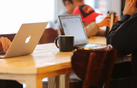 people sitting at a table working on their laptops and drinking coffee.