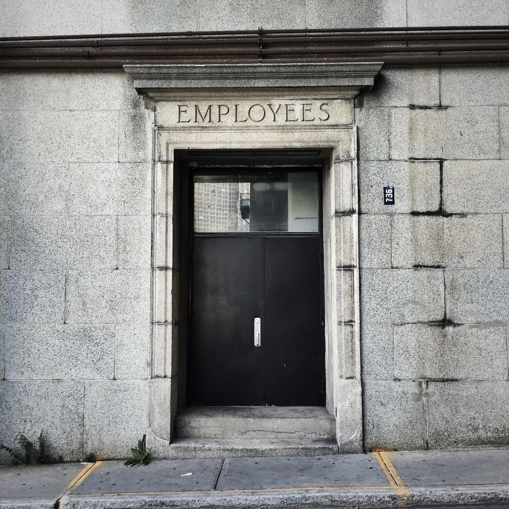 "Photo of an entrance to a stone building. The word ""employees"" is written above the door frame."