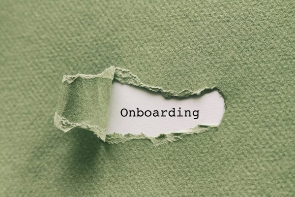 "Photo of a piece of green paper. A small portion of the paper is ripped and pulled back in the center, revealing the word ""onboarding"" underneath."