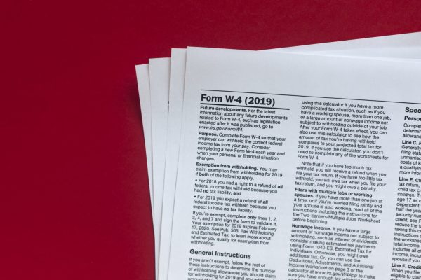 Photo of a stack of forms. On top is a W-4 exemption withholding form for the IRS.