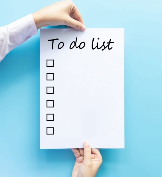 "Photo of a Caucasian individual's hands holding a large white piece of paper with the words ""To-Do List"" at the top. On the left side of the paper is a column of boxes to be checked off after completing tasks."