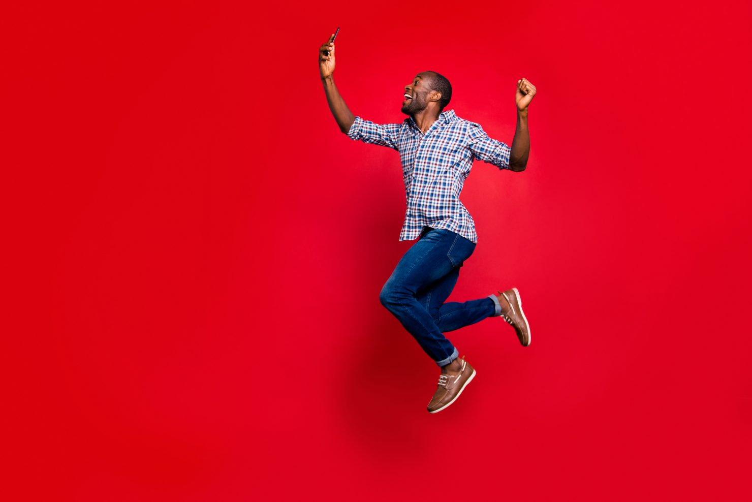 Photo of a young man of African descent jumping in the air while holding and looking at a cell phone. He is smiling and visibly happy. The backdrop is red.