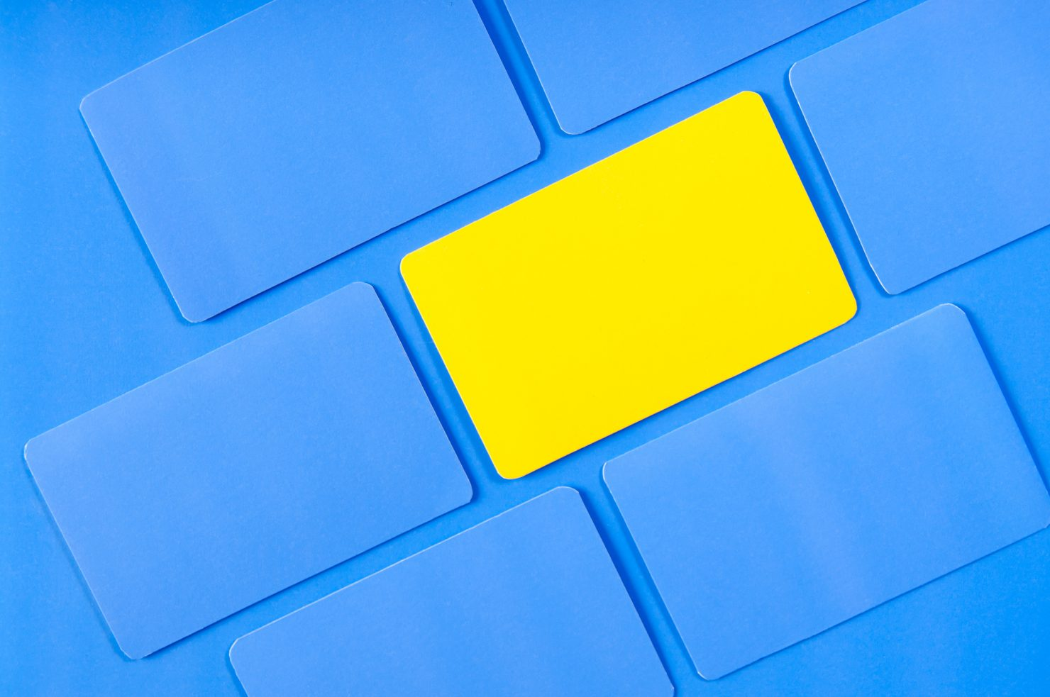 Photo of multiple square pieces of paper turned at an acute angle. All of the pieces of paper are blue save one in the middle which is yellow. This photo represents the importance of consistent visual branding.